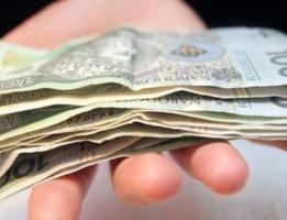 ręka z polskimi banknotami